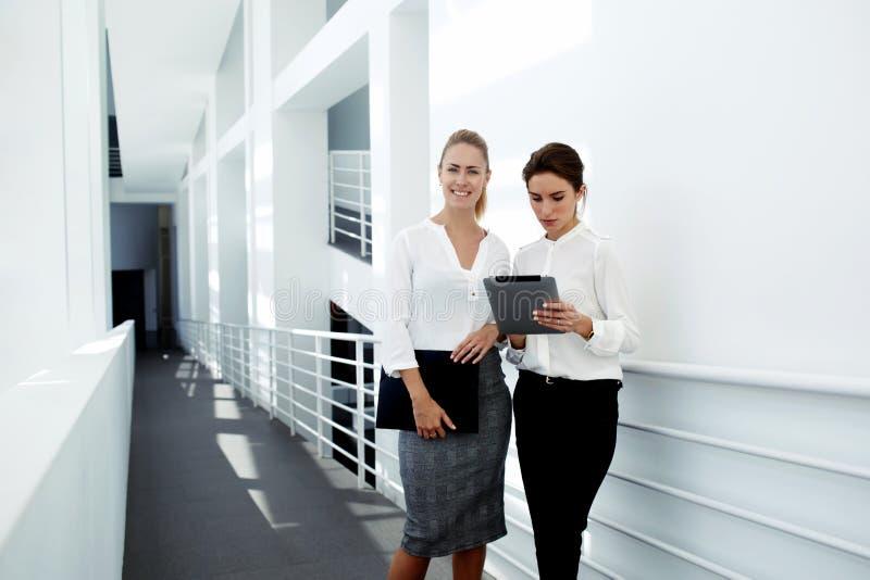 jeune femme d'affaires travaillant au pavé tactile tandis que son associé sûr se tenant proche et sourire photos stock