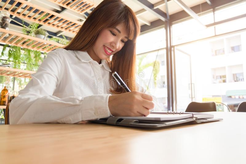 Jeune femme d'affaires travaillant avec l'ordinateur portable et les documents mobiles dedans image stock