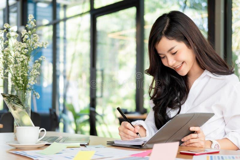 Jeune femme d'affaires travaillant avec l'ordinateur portable et les documents mobiles dedans photographie stock libre de droits