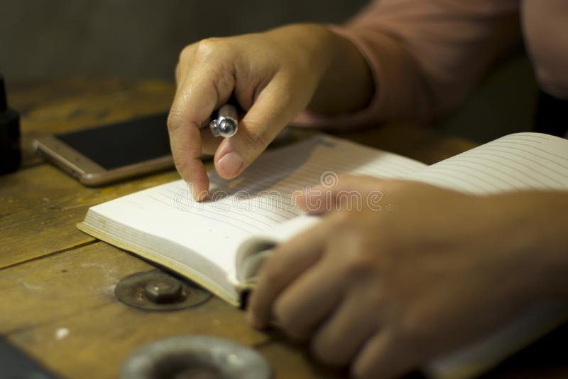 Jeune femme d'affaires travaillant avec un stylo au bureau, elle restant des heures suppl?mentaires image libre de droits