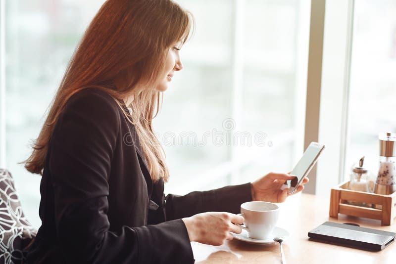 Jeune femme d'affaires utilisant son téléphone intelligent et sourire dans le café images stock