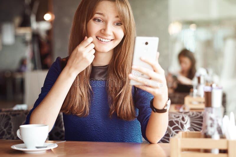 Jeune femme d'affaires utilisant son téléphone intelligent et sourire dans le café photographie stock