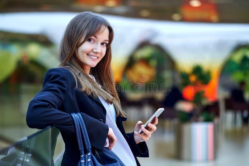 Jeune femme d'affaires utilisant son t?l?phone et sourire fut?s photo libre de droits