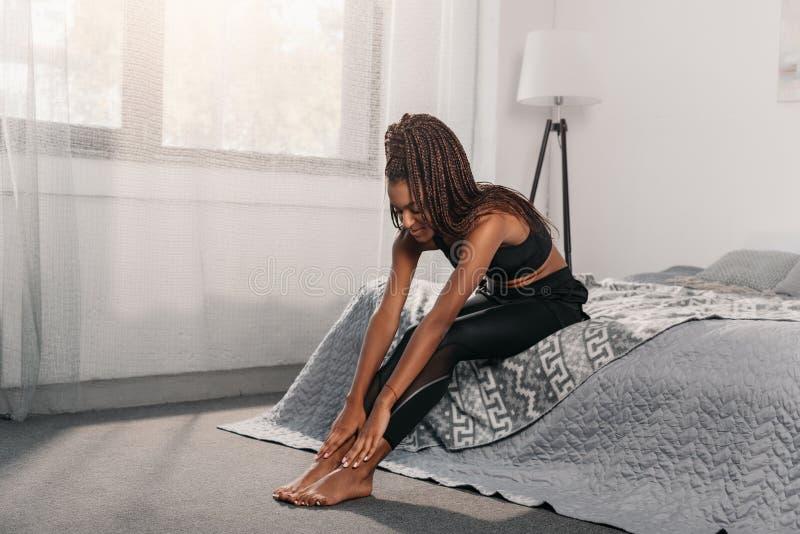 jeune femme d'afro-américain dans les vêtements de sport se reposant sur le lit et le contact images stock