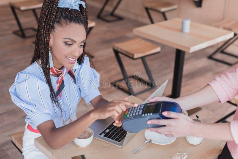 Jeune femme d'afro-américain payant avec la carte de crédit photos libres de droits