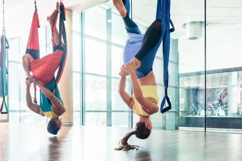 Jeune femme d'ajustement pratiquant le yoga aérien dans un centre de fitness moderne image libre de droits