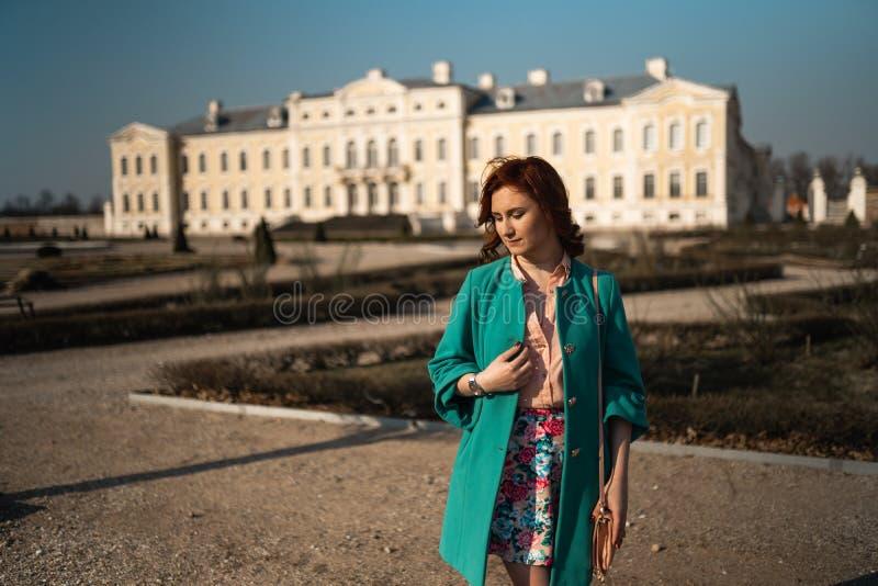 Jeune femme d'amant de mode waling en parc utilisant la veste verte vive et une jupe colorée photos libres de droits