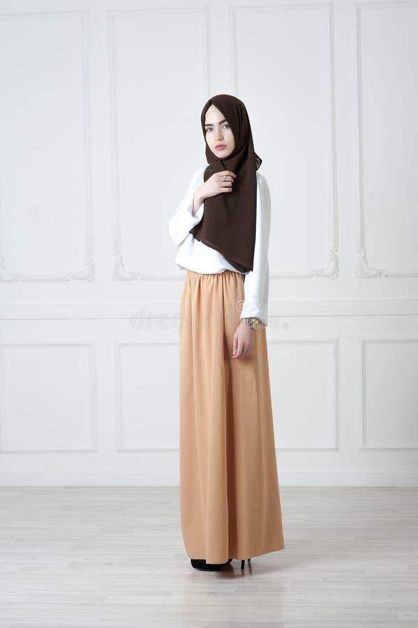 Jeune femme d'aspect du Moyen-Orient dans les vêtements musulmans modernes et l'écharpe noire, un fond classique clair photographie stock