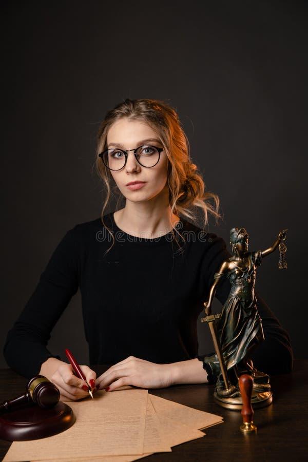 Jeune femme d'avocat dans une robe formelle et des lunettes se reposant à la table et écrivant quelque chose par le stylo, femme  photo libre de droits