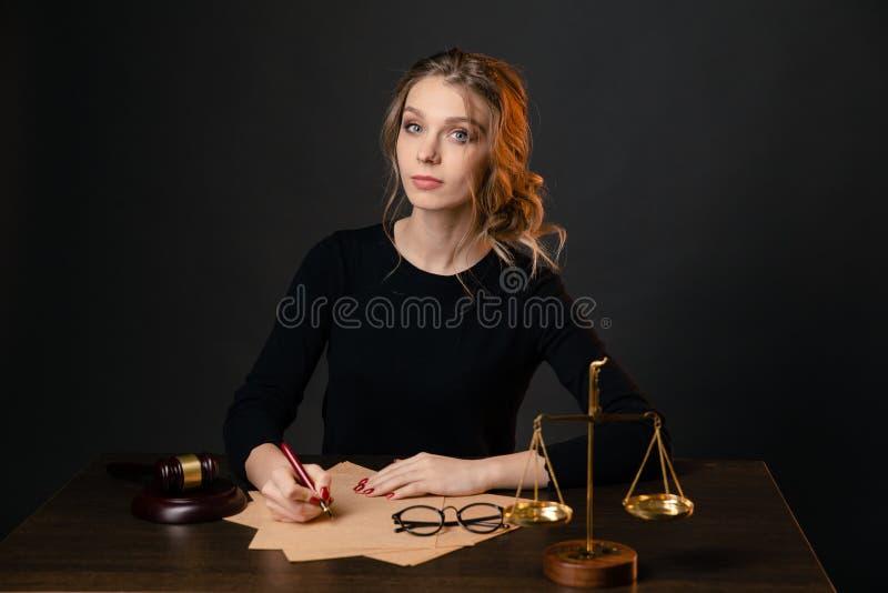 Jeune femme d'avocat dans une robe formelle se reposant à la table et écrivant quelque chose par le stylo, femme d'avocat avec le photographie stock libre de droits
