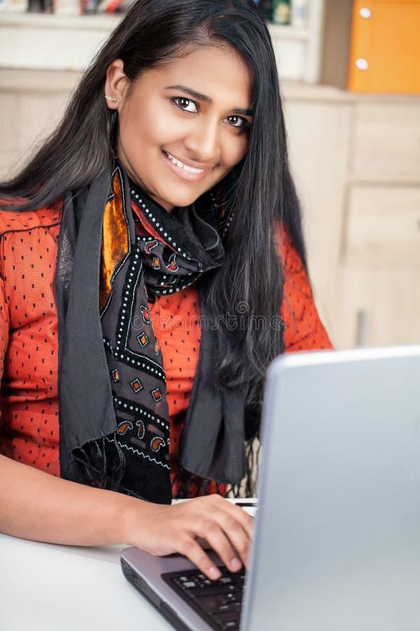 Jeune femme d'Inde avec l'ordinateur portable photographie stock libre de droits