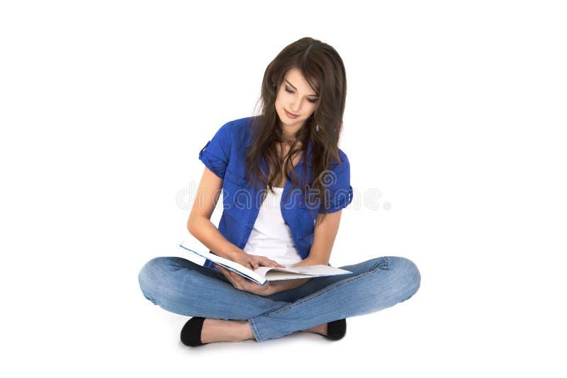 Jeune femme d'isolement avec le livre ouvert se reposant avec les jambes croisées. image libre de droits