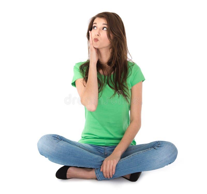 Jeune femme d'isolement s'asseyant dans des jambes croisées sur le plancher. photographie stock