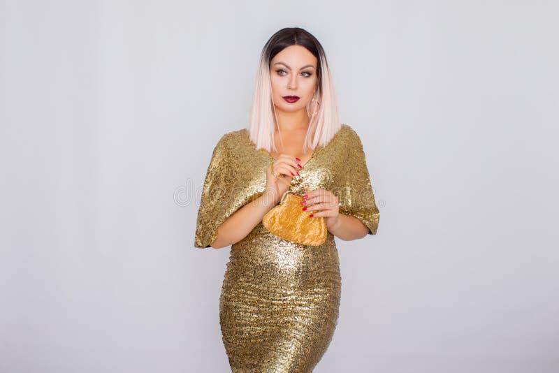 Jeune femme d'une chevelure blonde de charme portant la robe et tenir de soirée élégante d'or l'embrayage de couleur d'or dans de image libre de droits