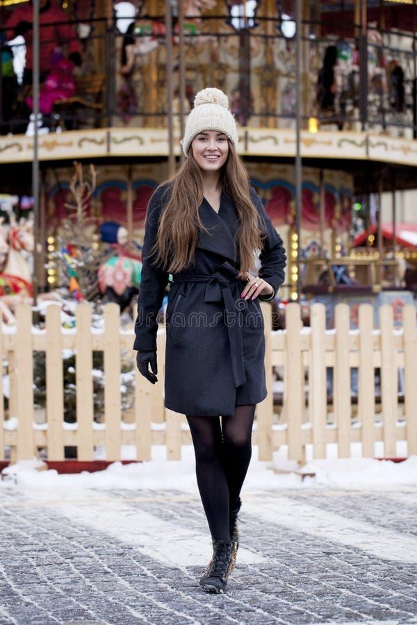 Jeune femme d'une chevelure brune heureuse sur le fond d'un amu d'hiver photographie stock