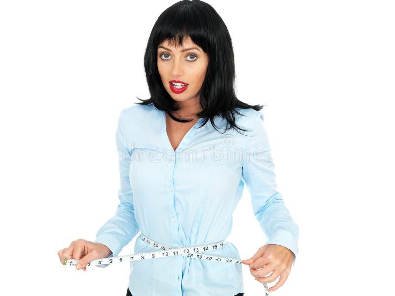 Jeune femme d'une chevelure foncée mesurant sa taille avec un ruban métrique images libres de droits