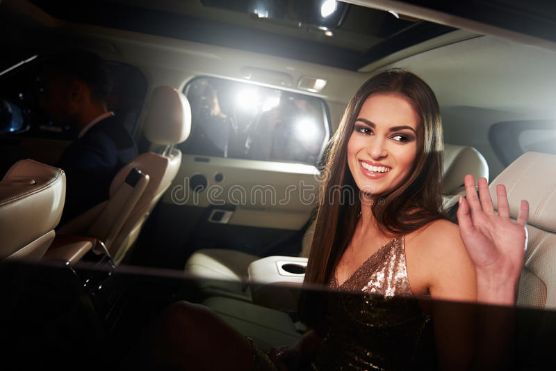 Jeune femme d'une chevelure foncée ondulant de derrière d'une limousine image libre de droits