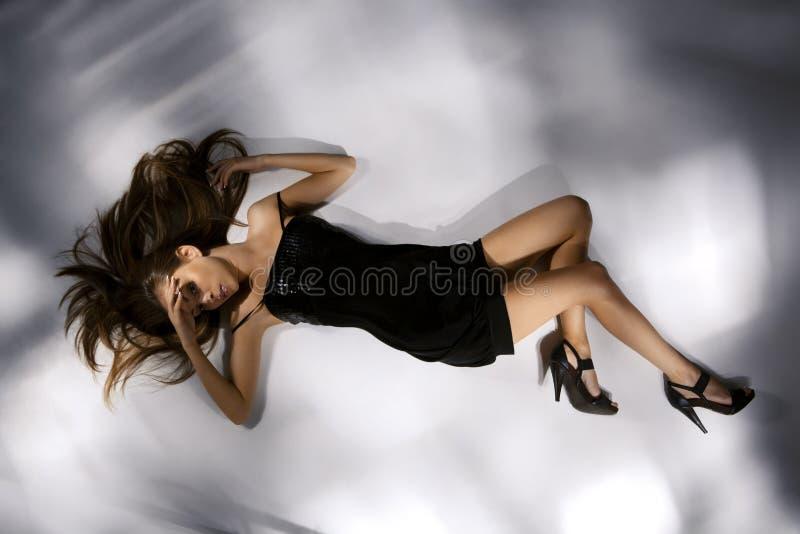 Jeune femme d'une manière élégante belle dans la robe noire photographie stock