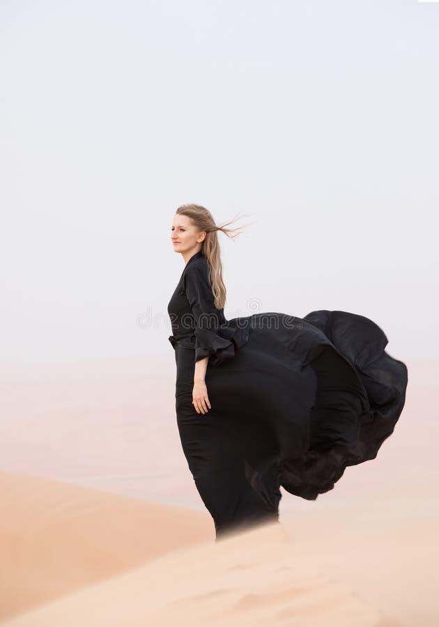 Jeune femme dans Abaya posant dans le paysage de désert photos stock