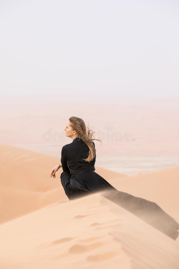 Jeune femme dans Abaya posant dans le paysage de désert photographie stock libre de droits