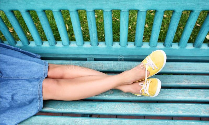 Jeune femme dans des chaussures en caoutchouc se reposant sur le banc dehors images stock