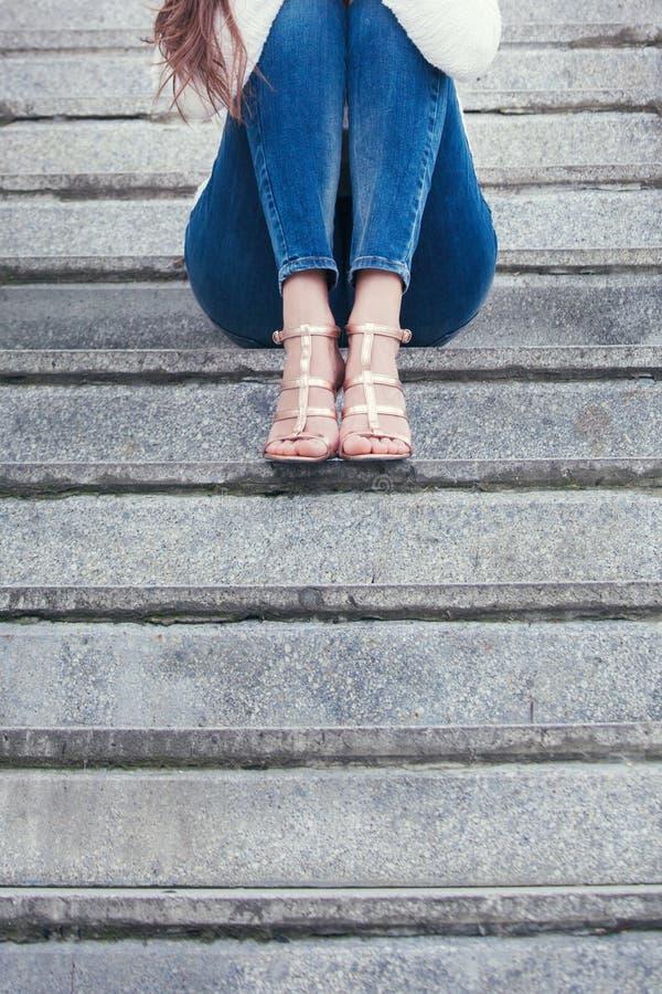 Jeune femme dans des chaussures et des blues-jean de talon haut sur la partie inf?rieure du corps tir?e ext?rieure d'escaliers photo libre de droits