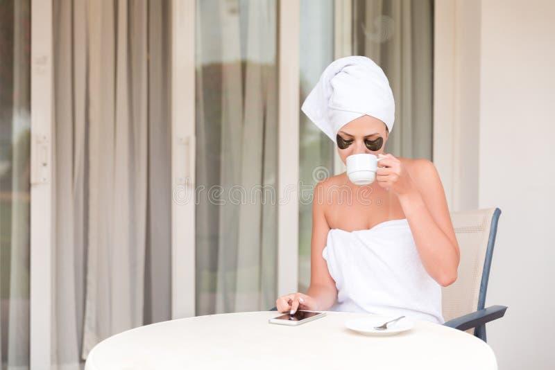Jeune femme dans des corrections de sous-oeil ?crivant le message de sms et buvant du caf? ? la station de vacances de terrasse d photos stock
