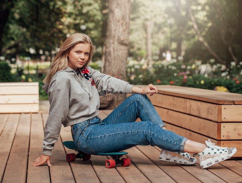 Jeune femme dans des jeans se reposant sur la planche à roulettes en parc lifestyle Poils de vol image stock