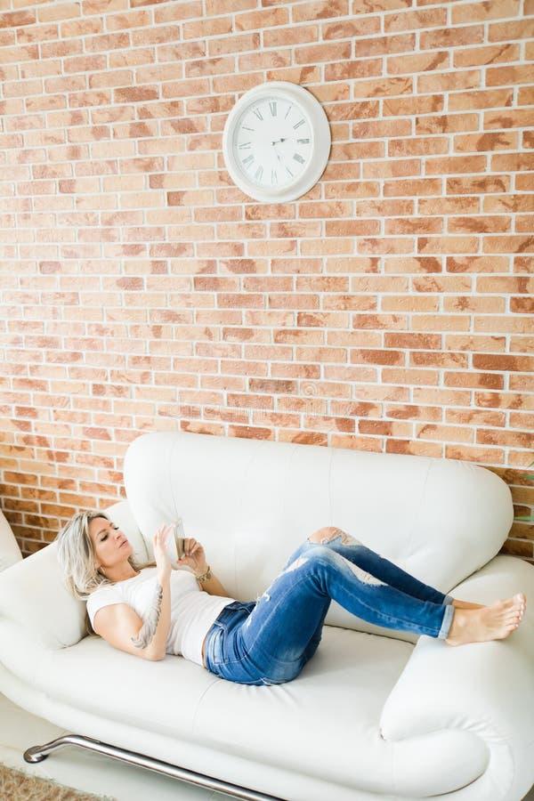 Jeune femme dans des jeans utilisant le téléphone intelligent se trouvant confortablement sur le sofa blanc photos stock