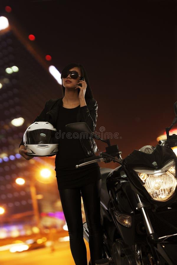 Jeune femme dans des lunettes de soleil parlant sur le téléphone et la position près de sa moto la nuit dans Pékin image stock