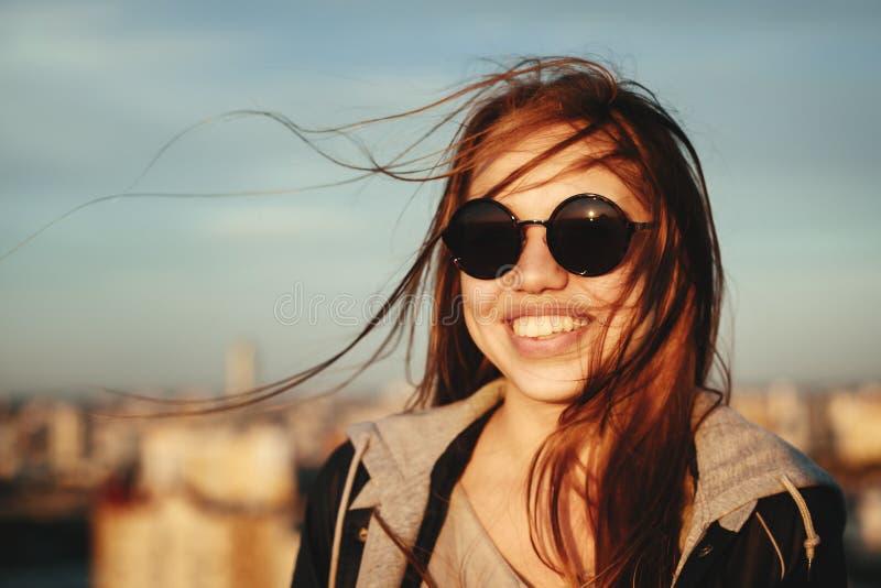 Jeune femme dans des lunettes de soleil rondes ayant l'amusement images stock