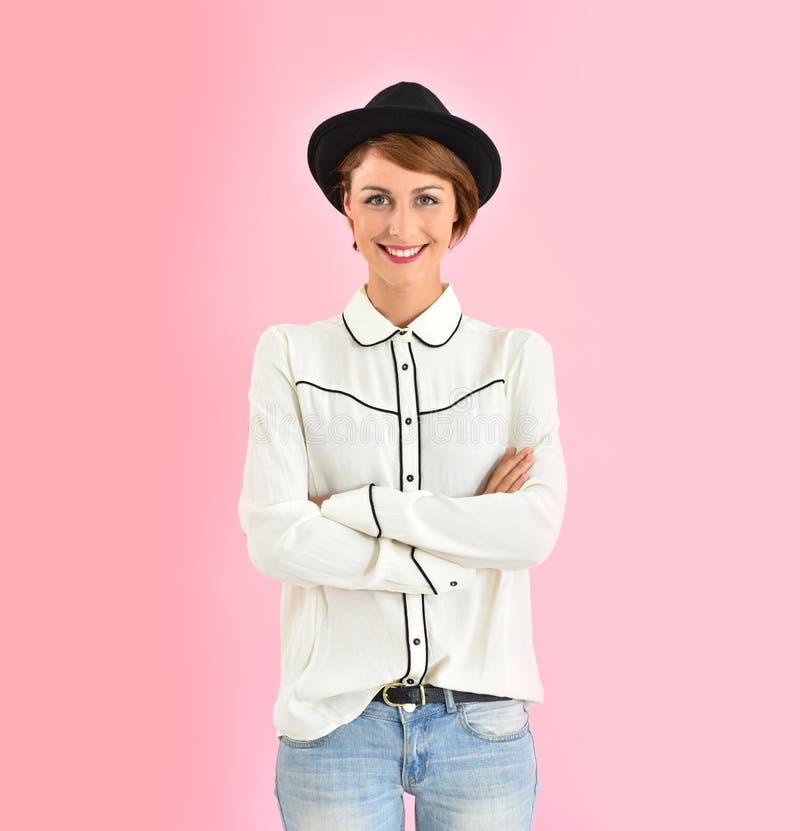 Jeune femme dans des vêtements à la mode utilisant le chapeau noir image libre de droits