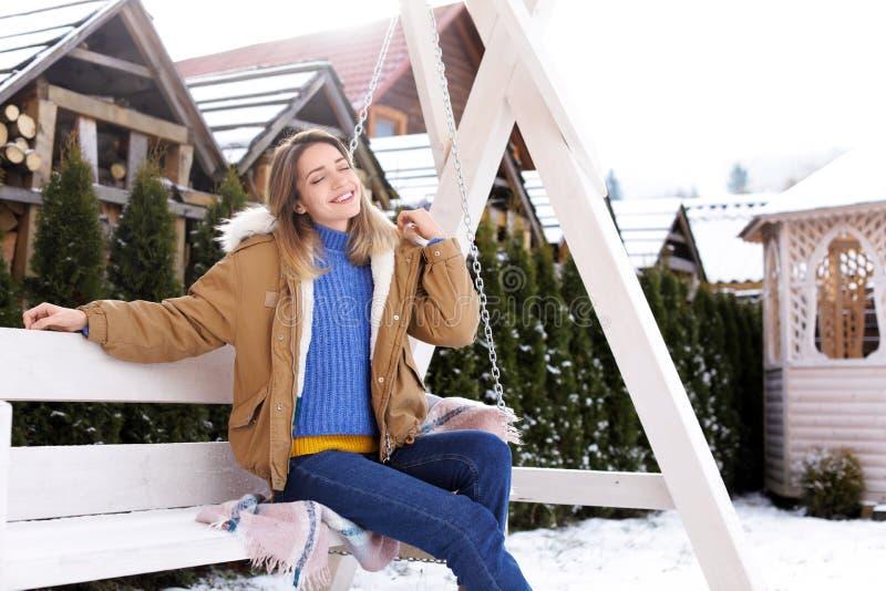 Jeune femme dans des vêtements chauds se reposant sur extérieur Vacances de l'hiver photos stock