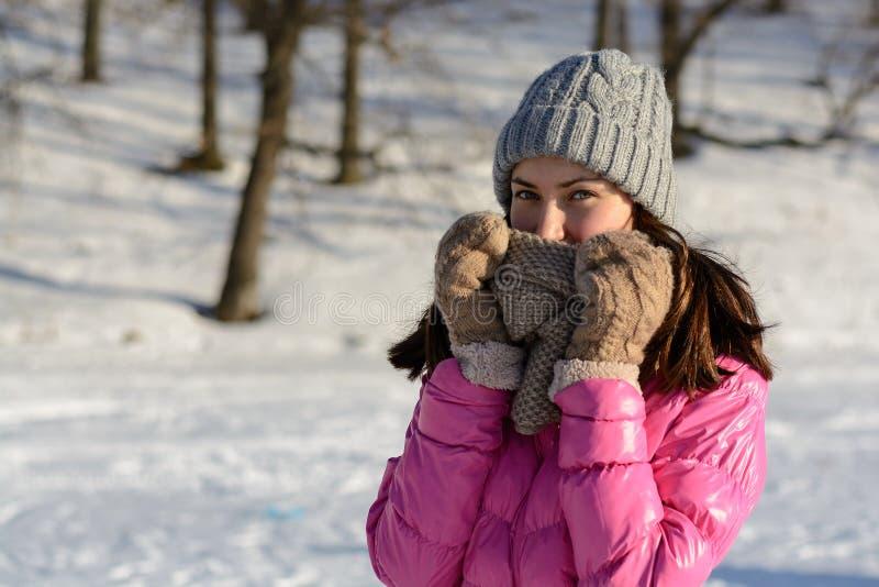 Jeune femme dans des vêtements d'hiver à l'arrière-plan de la brune de forêt dans le rose en bas de la veste, du chapeau tricoté, photos stock