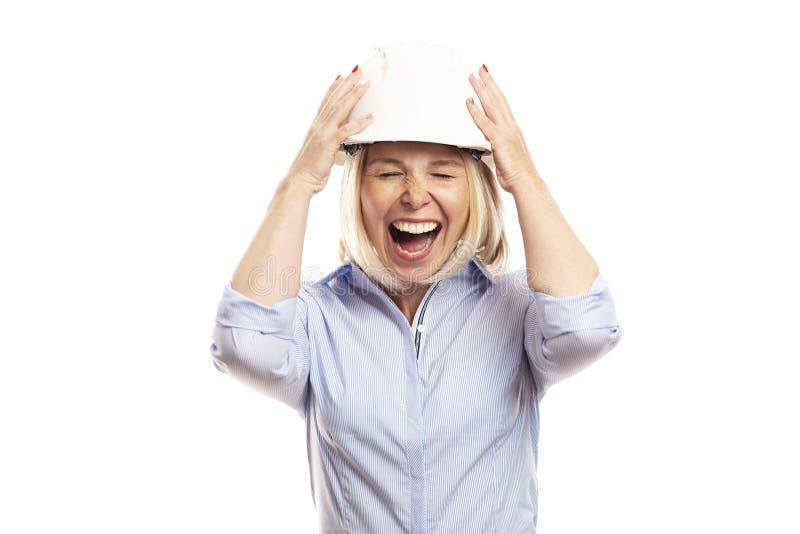 Jeune femme dans des vêtements de bureau et un casque de construction sur son chef criant Plan rapproch? Fond blanc photographie stock