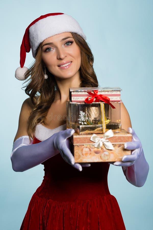 Jeune femme dans des vêtements de Santa Claus avec des cadeaux photos stock