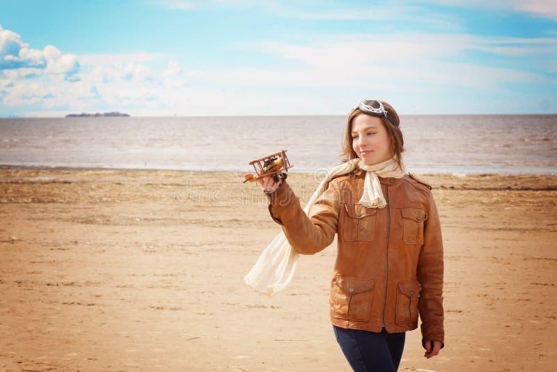 Jeune femme dans des vêtements pilotes du ` s jouant avec l'avion en bois sur le rivage arénacé de baie image libre de droits