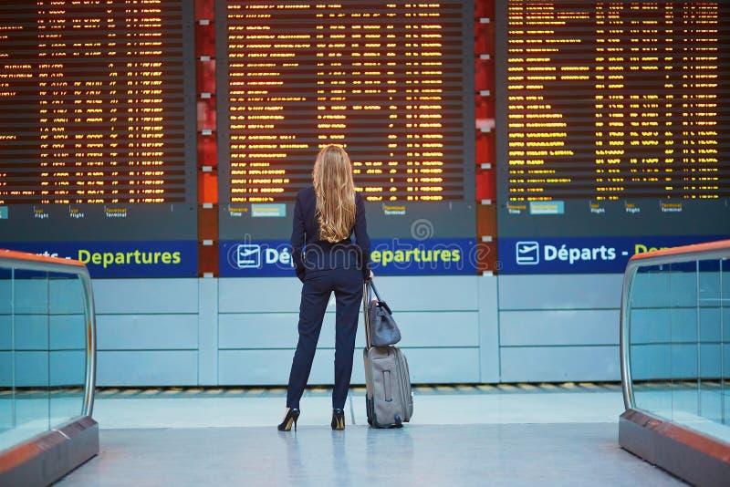 Jeune femme dans l'aéroport international regardant le conseil de l'information de vol, vérifiant son vol photographie stock