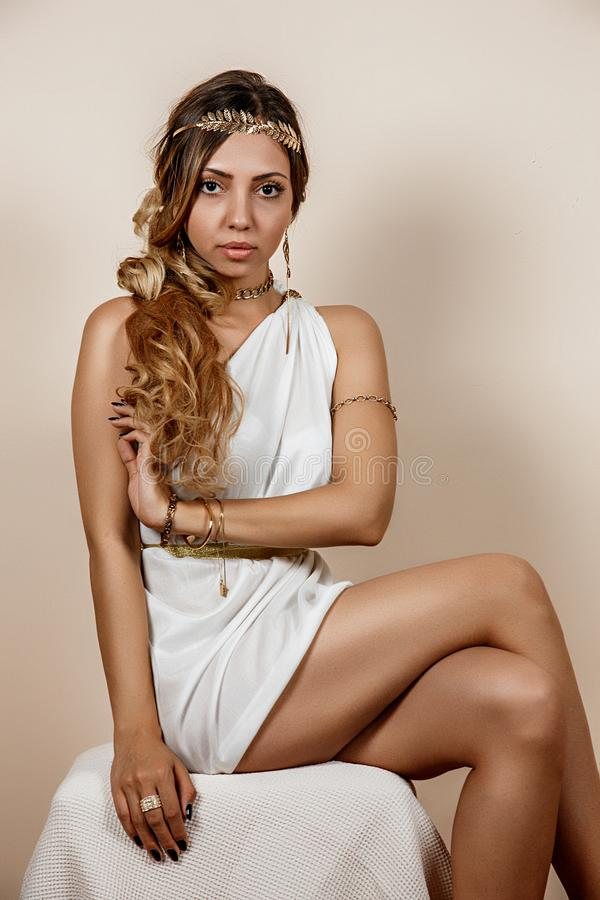 Jeune femme dans l'habillement grec de style au-dessus du fond beige photo stock