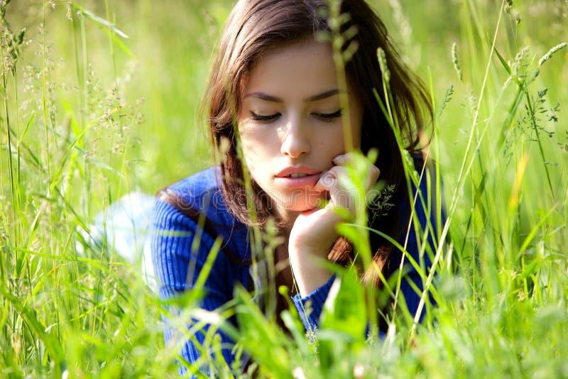 Jeune femme dans l'herbe image stock