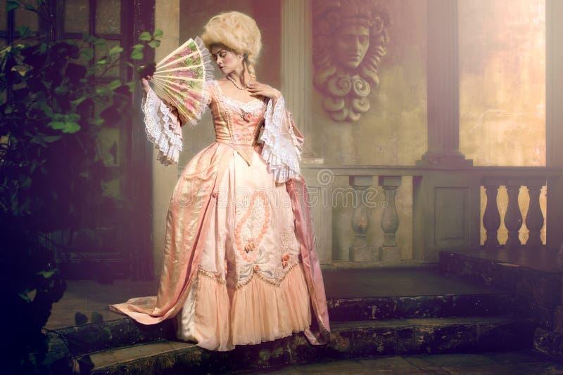 Jeune femme dans l'image du 18ème siècle posant dans l'extérieur de vintage image stock