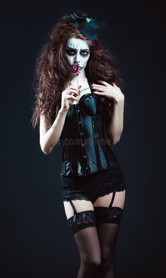 Jeune femme dans l'image du clown anormal gothique triste sentant la fleur défraîchie images libres de droits