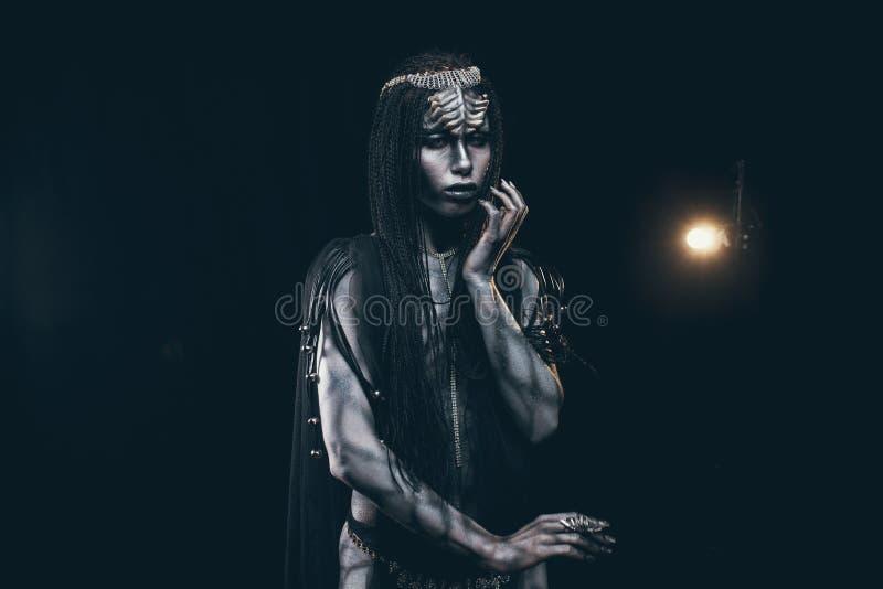 Jeune femme dans l'image du humanoïde et de l'étranger extraterrestre sur b image stock