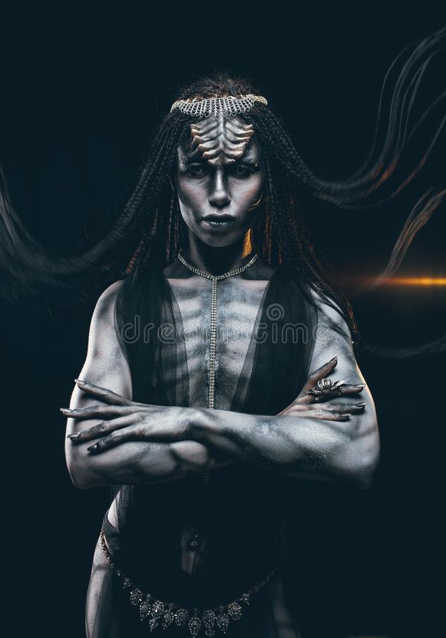 Jeune femme dans l'image du humanoïde et de l'étranger extraterrestre sur b photos stock