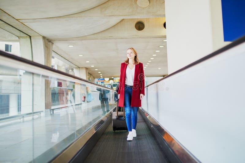 Jeune femme dans l'a?roport international avec le bagage image stock
