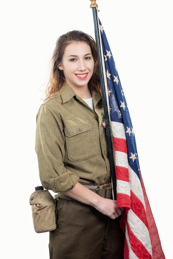 Jeune femme dans l'uniforme militaire des USA supportant un drapeau américain image libre de droits