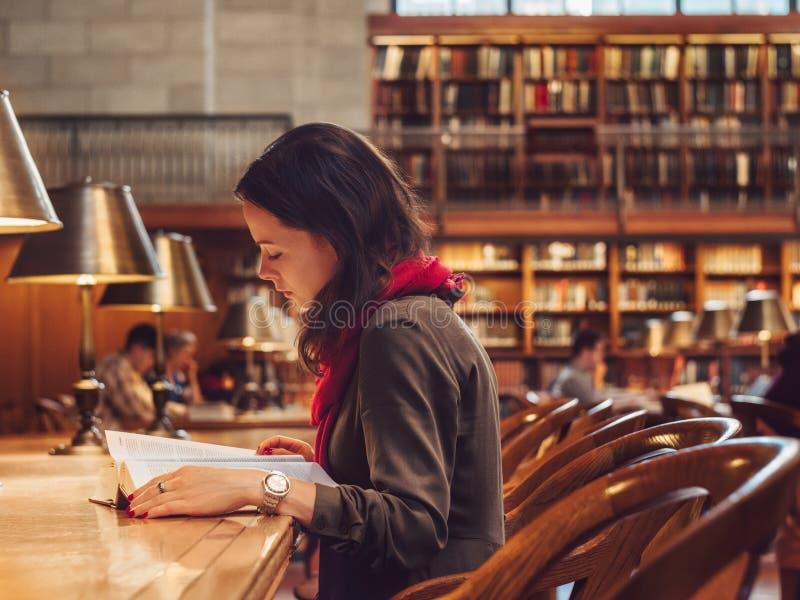 Jeune femme dans la bibliothèque photos stock