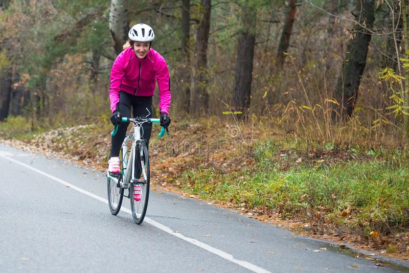 Jeune femme dans la bicyclette rose de route d'équitation de veste en parc dans Autumn Day froid Style de vie sain photographie stock libre de droits