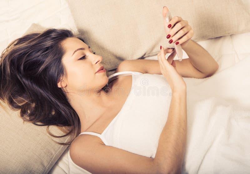 Jeune femme dans la chambre à coucher avec le téléphone portable dans la chambre à coucher images stock