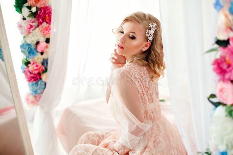 Jeune femme dans la chambre décorée des fleurs photos stock